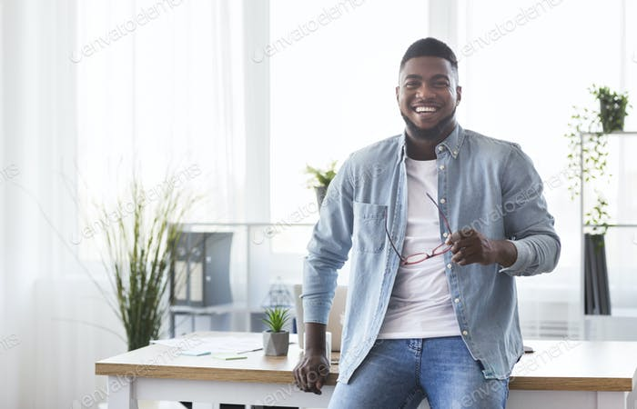 Successful businessman leaning on office desk and looking at camera