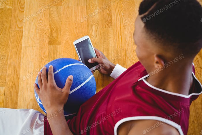 Overhead view of male basketball player using mobile phone
