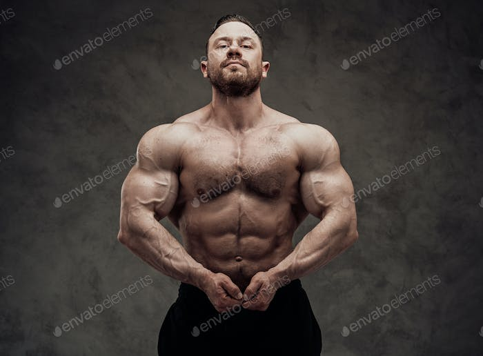 Athletic man isolated on a grey background is showing his chest muscle