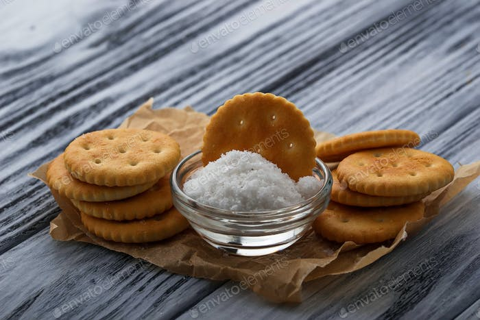 Salty cracker and salt on wooden background