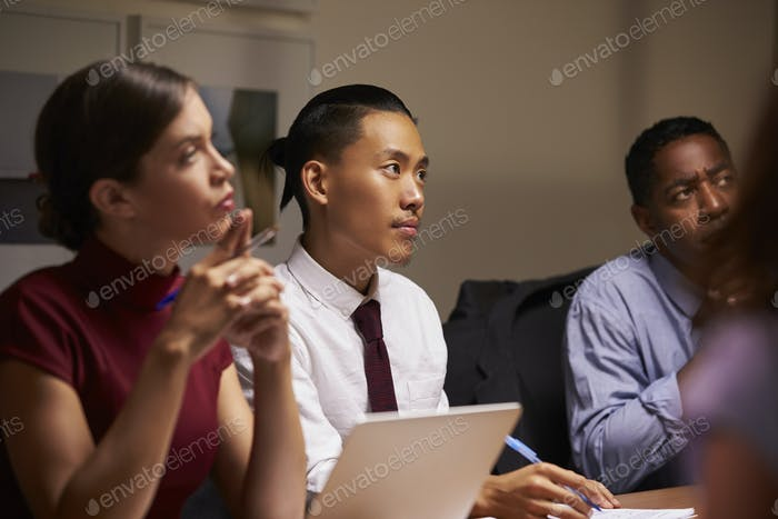 Business colleagues listening at evening meeting, close up