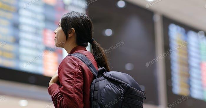 Mujer comprobar el número de vuelo en el aeropuerto
