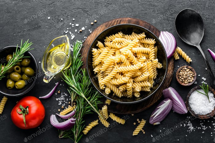 Pasta and ingredients for cooking on black background, top view. Italian food