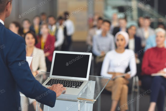 Mixed race businessman using laptop while he speaks at a business seminar in modern office building