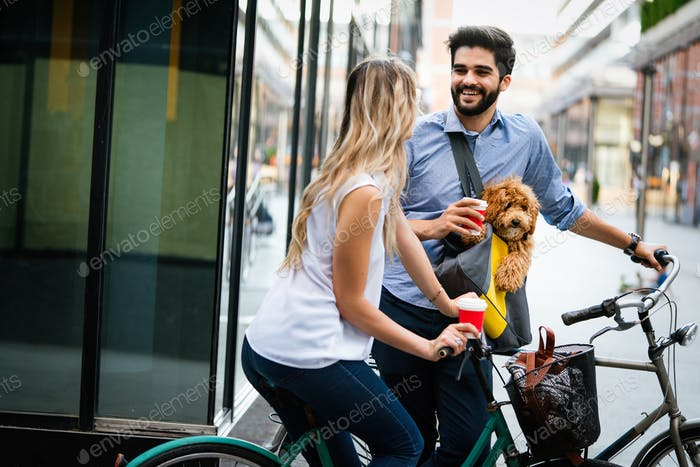 Laughing young couple with small dog walking in the city
