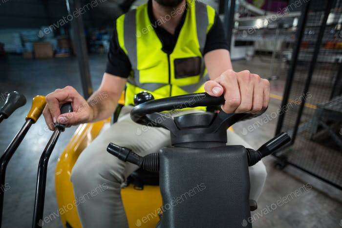 Factory worker driving forklift in factory