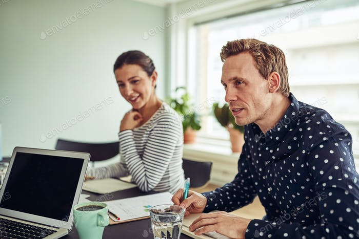 Two smiling businesspeople talking with colleagues during an office meeting