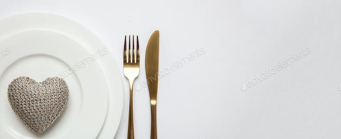 Table setting, wedding reception. Gold cutlery on white set of dishes, white background