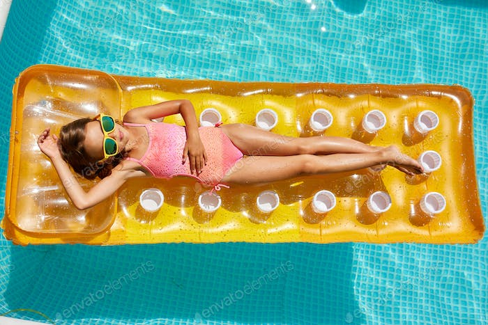 Little girl in sunglasses relaxing in swimming pool, swims on inflatable yellow mattres