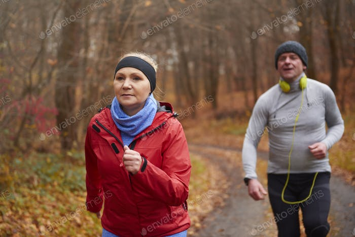 Mature couple running through forest path