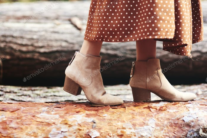 Boots of woman in autumnal forest