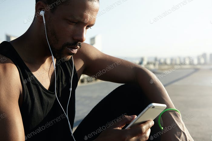 Nice photo of young and handsome athlete choosing musical track for running on digital device. Lonel
