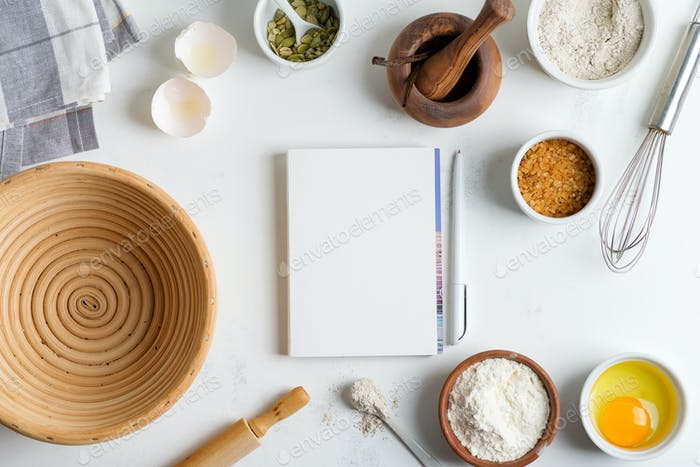 Baking ingredients for cooking homemade traditional bread with paper for recipe on a light grey