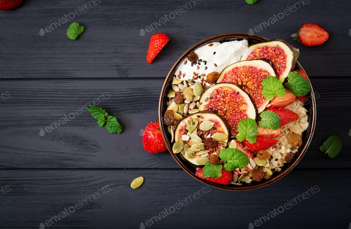 Delicious and healthy oatmeal with figs, seeds, strawberry and yogurt.