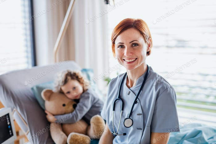 Friendly female doctor and small girl in bed in hospital.