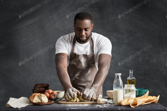 Black male cook wears apron, stands near table with products, shoots video lesson how to make dough