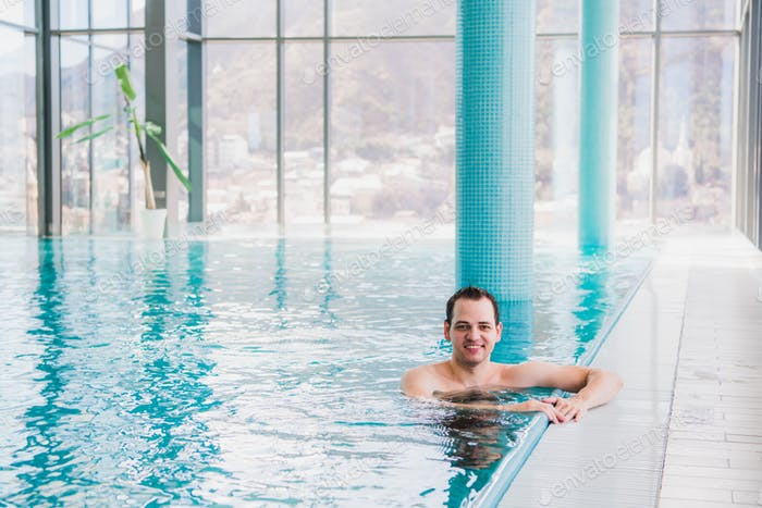 Shot of a handsome young happy man in the indoor swimming pool