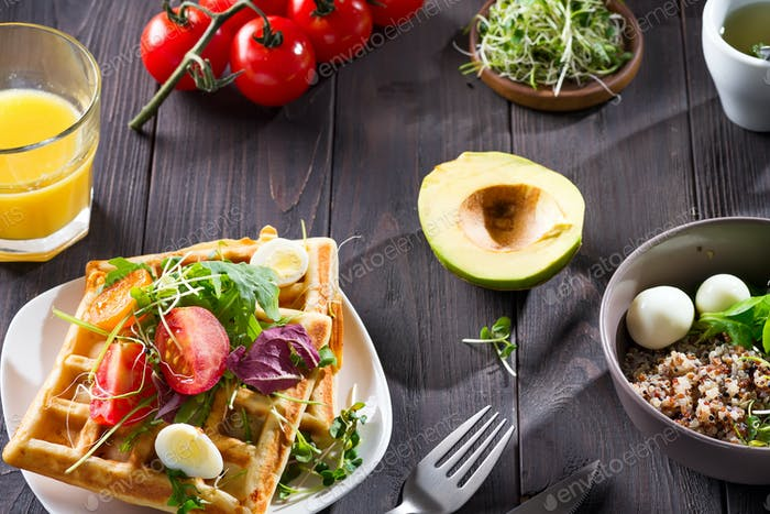 Morning healthy breakfast with vegetables salad on homemade waffles, greenery and cut avocado on a