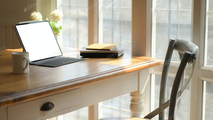 Cropped shot of classic workplace with laptop,coffee cup and stationary on wooden table.