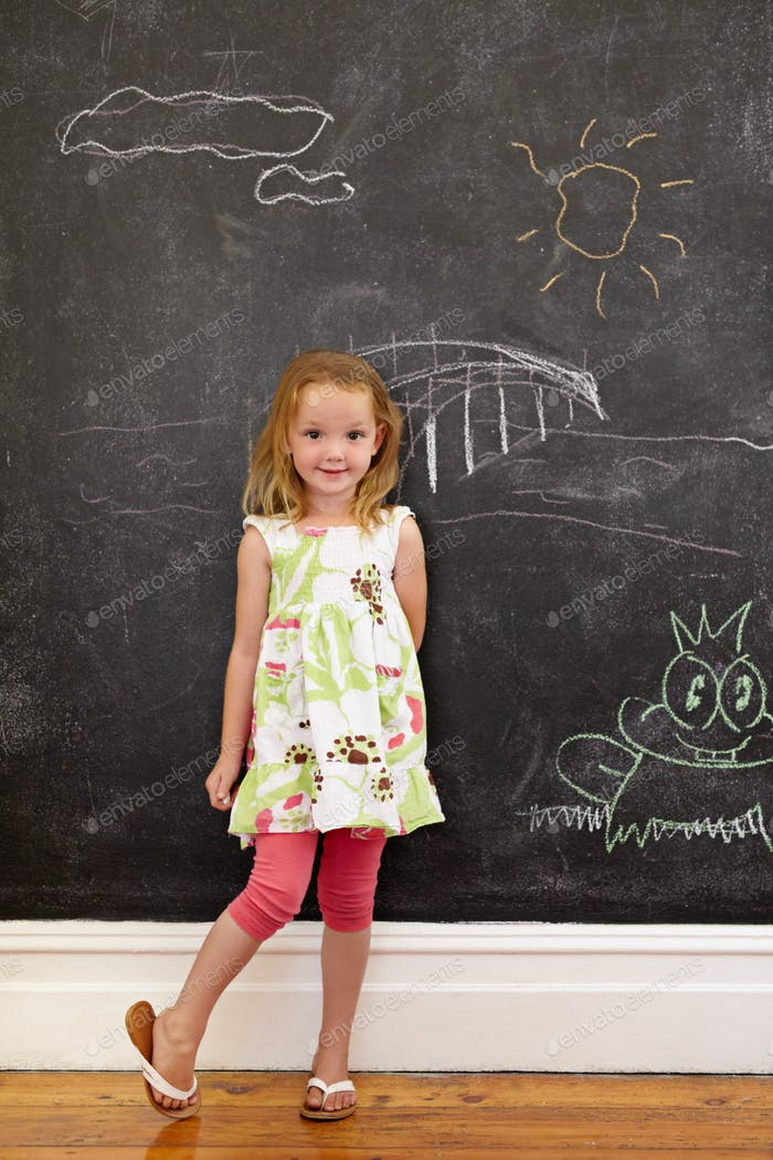 Innocent little girl standing with chalk drawings at home