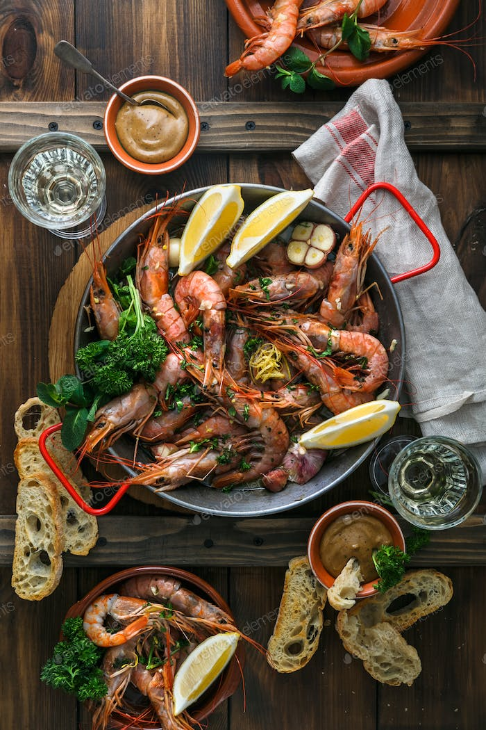 Paella pan with roasted tiger prawns and many dishes, bread and wine