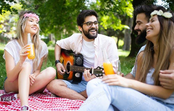 Glückliche Gruppe von Freunden entspannen und Spaß am Picknick in der Natur haben