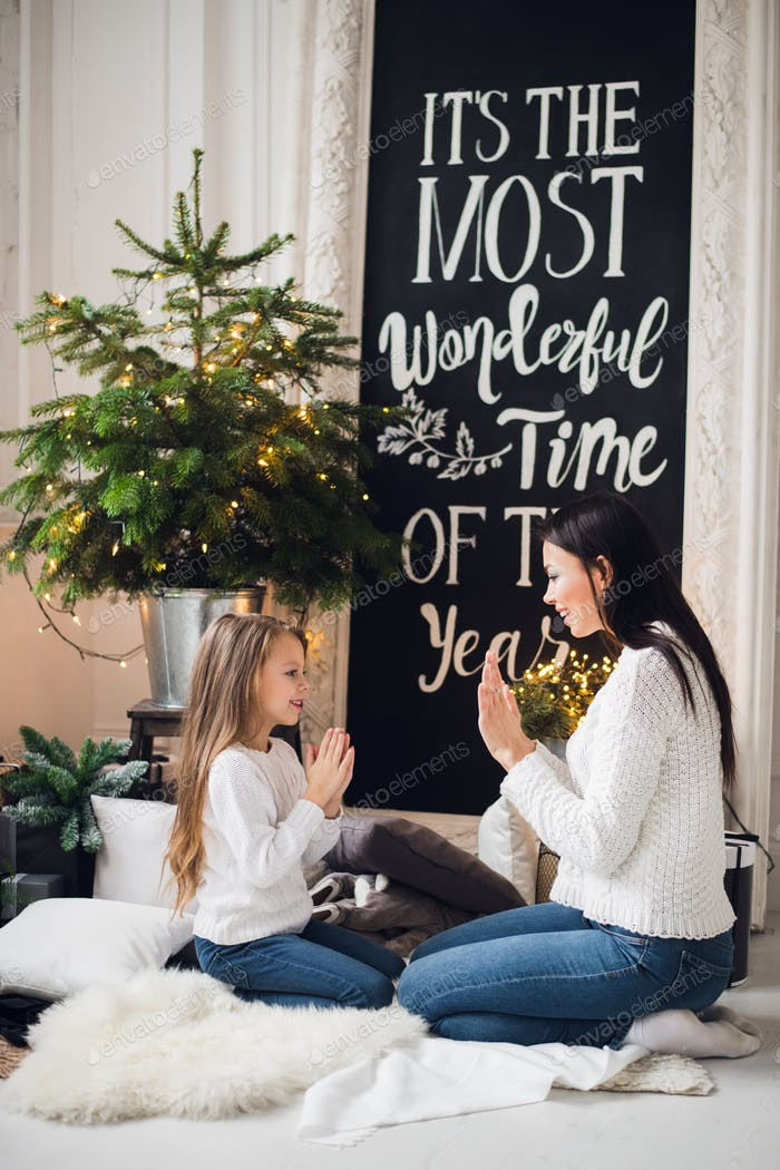 Young stylish pretty woman congratulates daughter in dress on xmas playing with hands at home