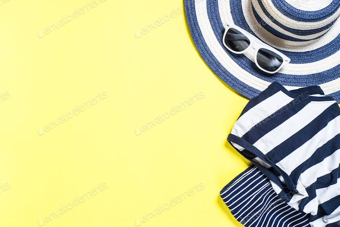 Woman summer cloth set - hat, dress and sunglasses on yellow background.