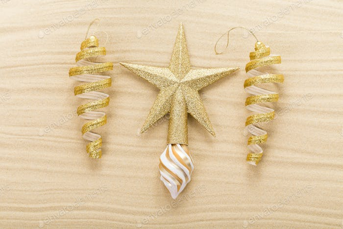 Christmas star and decorations on sand.