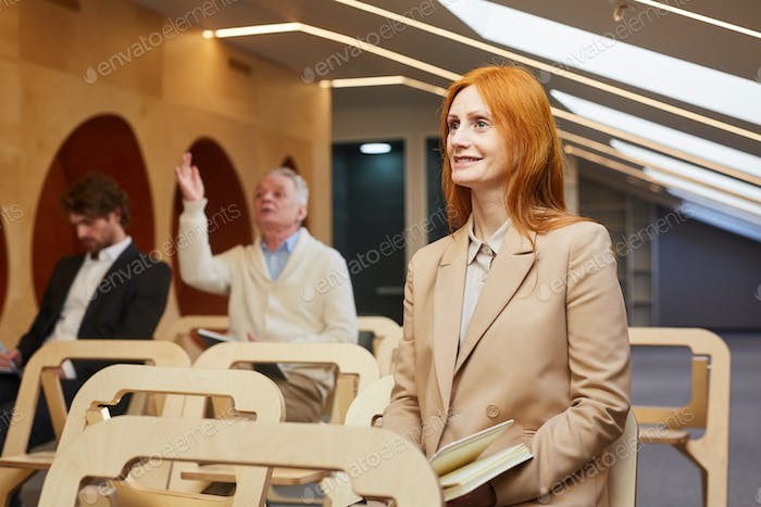 Smiling Adult Businesswoman in Seminar Audience