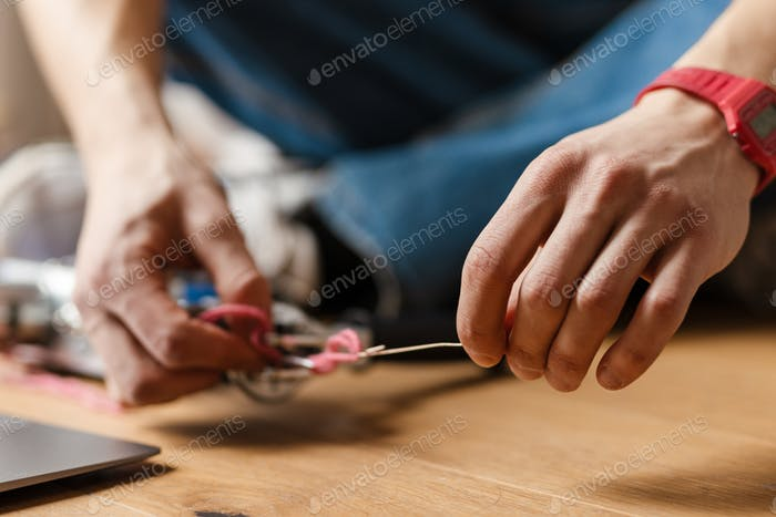 Young white man working with sewing machine indoors