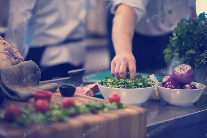 chef hand serving vegetable salad