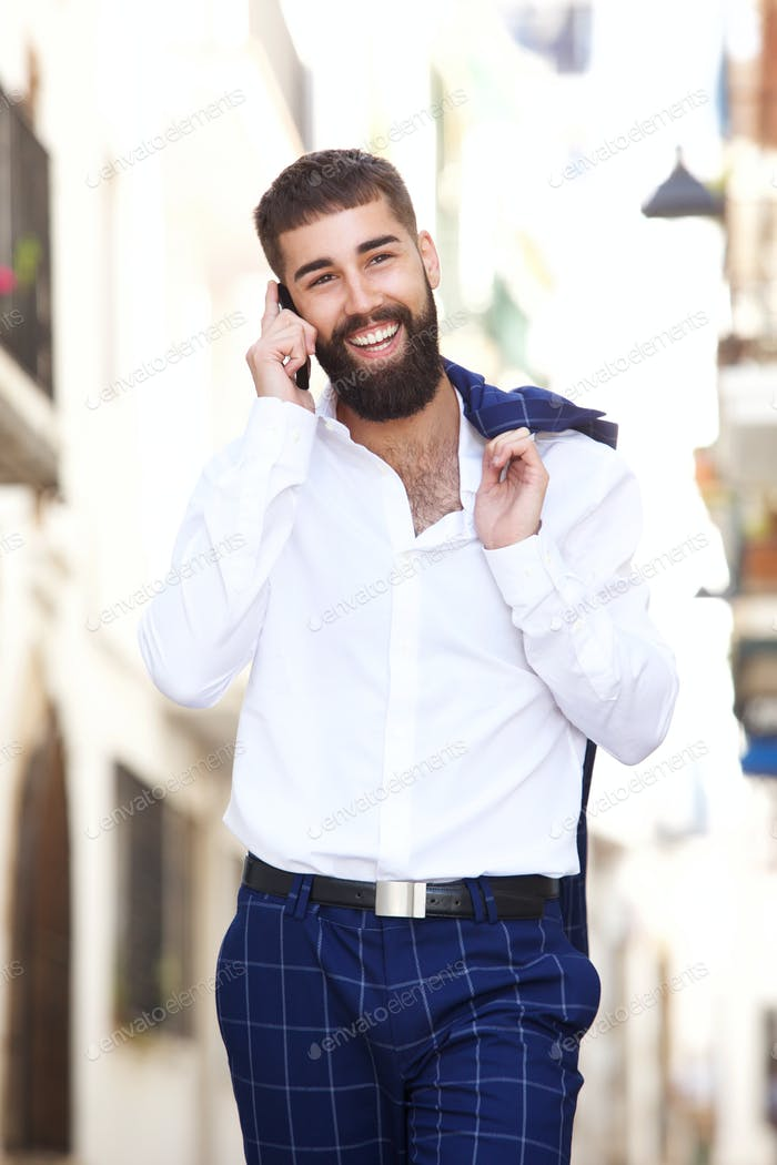 Happy businessman walking in city and talking on smart phone
