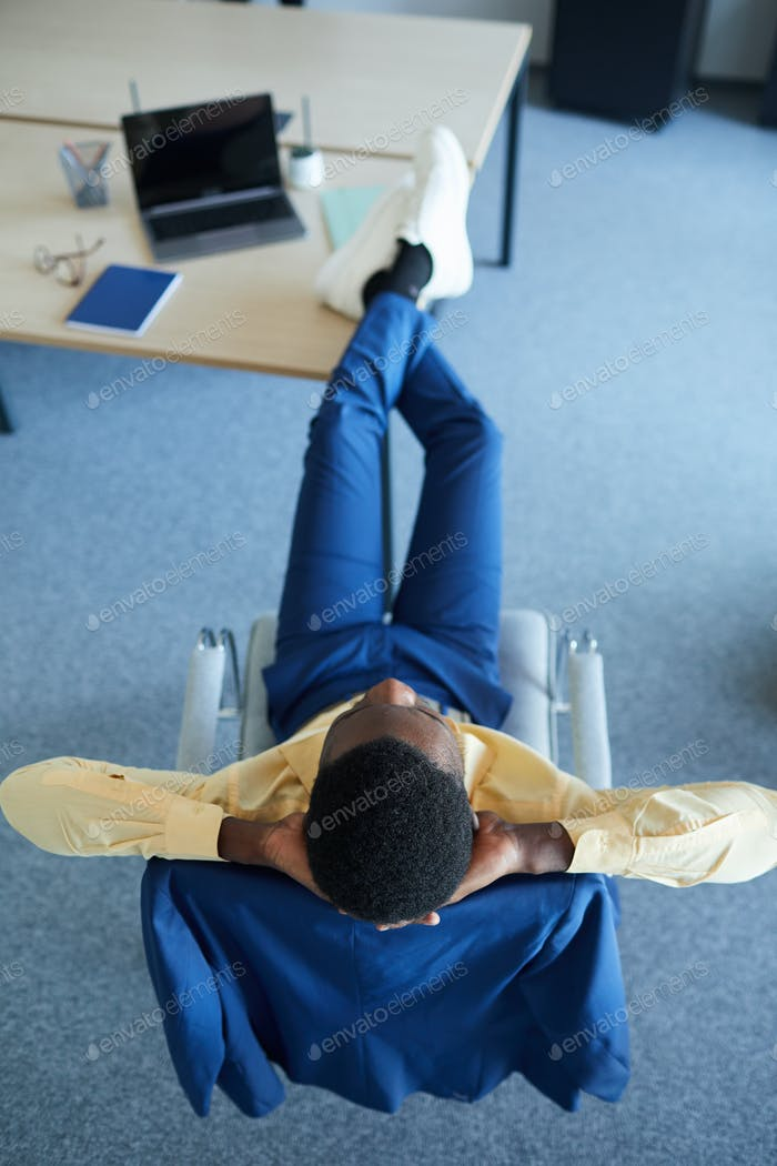 African Businessman Relaxing at Workplace