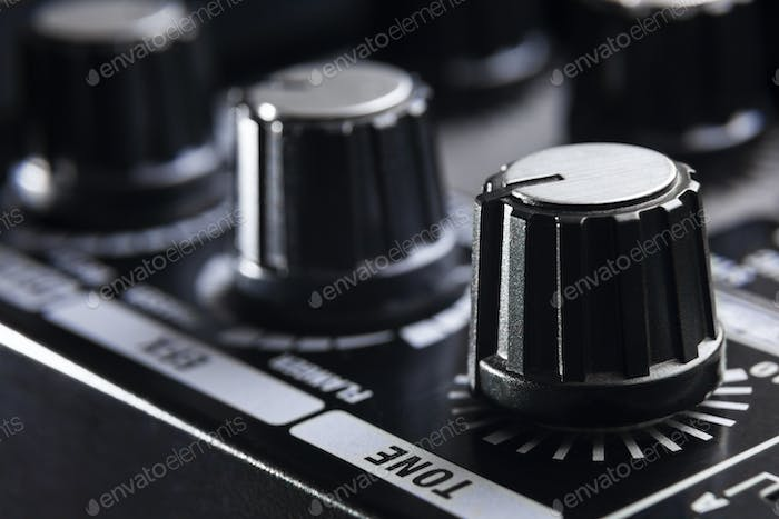 close-up detail of the adjustment knobs in the panel of an electric guitar amplifier