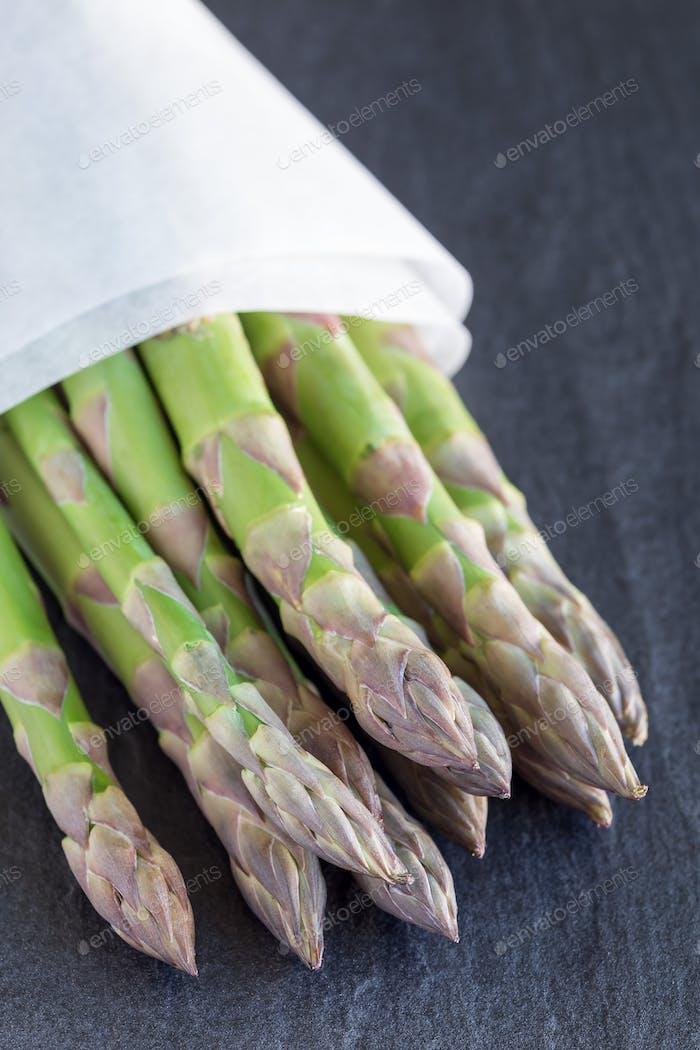Bunch of fresh green asparagus on a dark slate background, verti