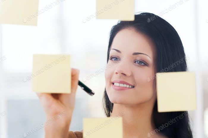 Escribir nuevas ideas. Mujer joven hermosa escribiendo nuevas ideas en notas adhesivas