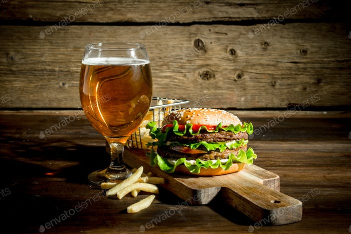 Burger with beer in a glass and fries.