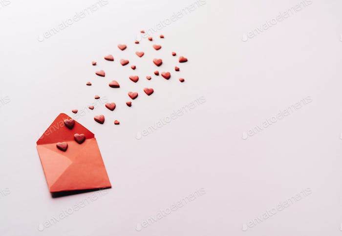 Small hearts fly out of a small red envelope. Valentine's Day conceptual Background.