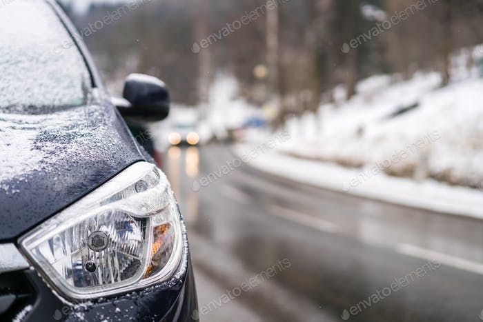 Close up of a light of a car parked on the roadside in winter