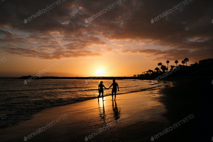 Romantic couple on the beach in a colorful sunset in the background.A guy and a girl at sunset on