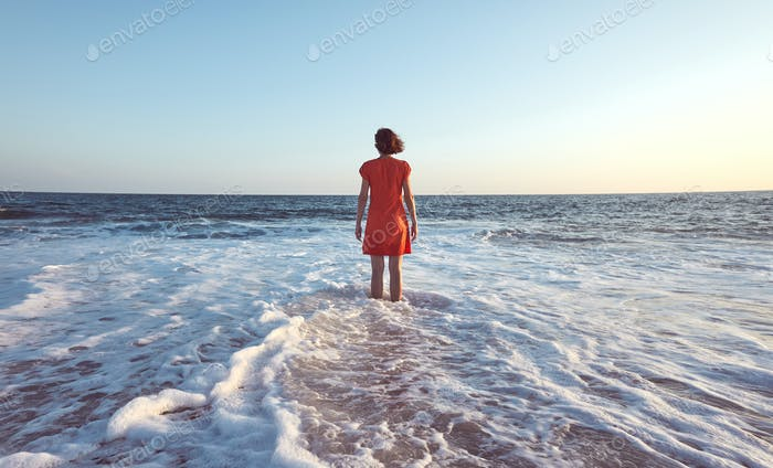 Woman standing in the ocean at sunset.