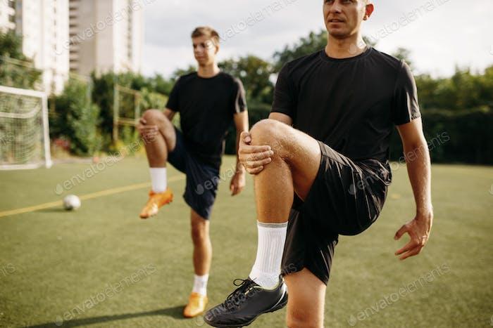 Männliche Fußballspieler tun Stretching Übung