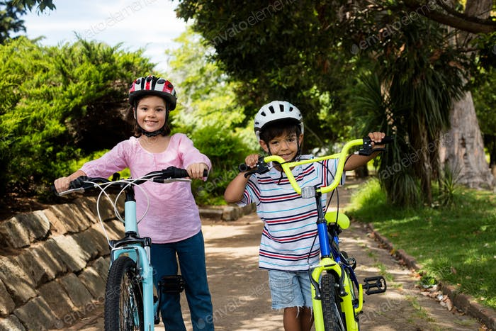 Portrait of smiling children standing with bicycle in park