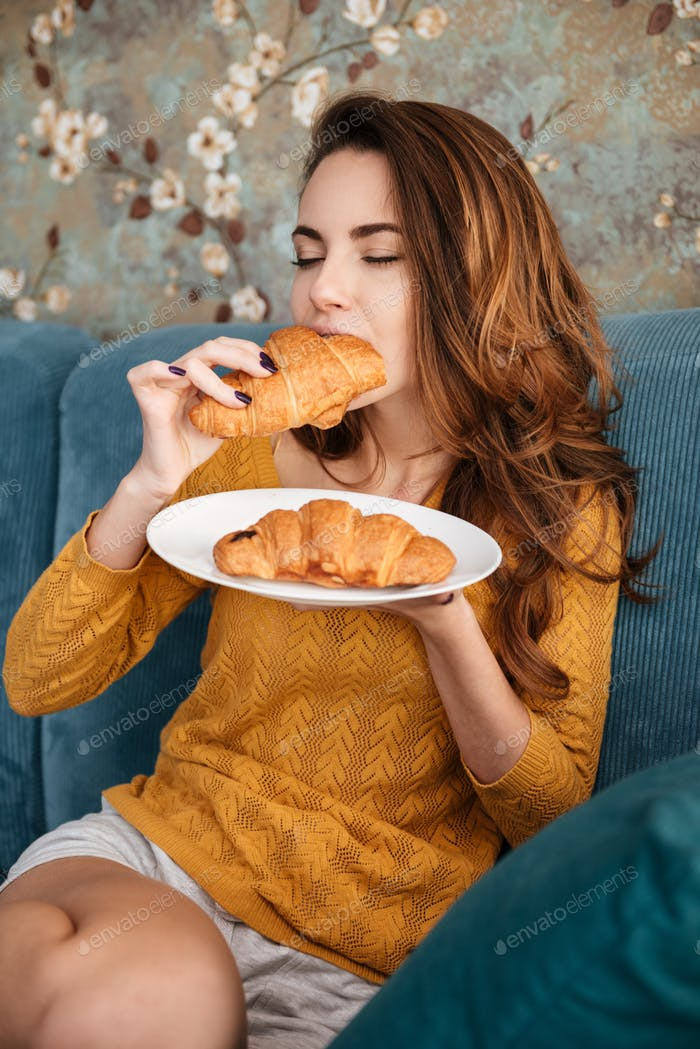 Portrait of a smiling attractive woman eating croissant