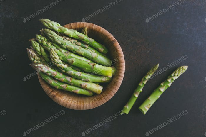 Fresh asparagus in a wooden bowl on a table