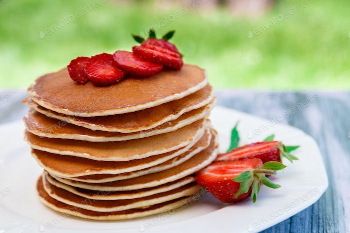 Pancakes with fresh strawberry and mint on white plate on pink wooden background in garden