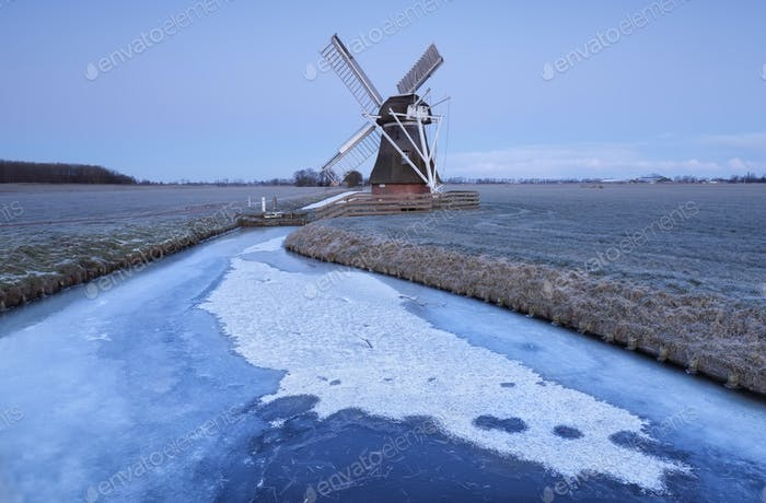Dutch windmill in dusk by frozen river in winter