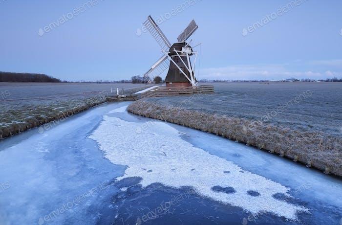 Molino de viento holandés al atardecer por río congelado en invierno