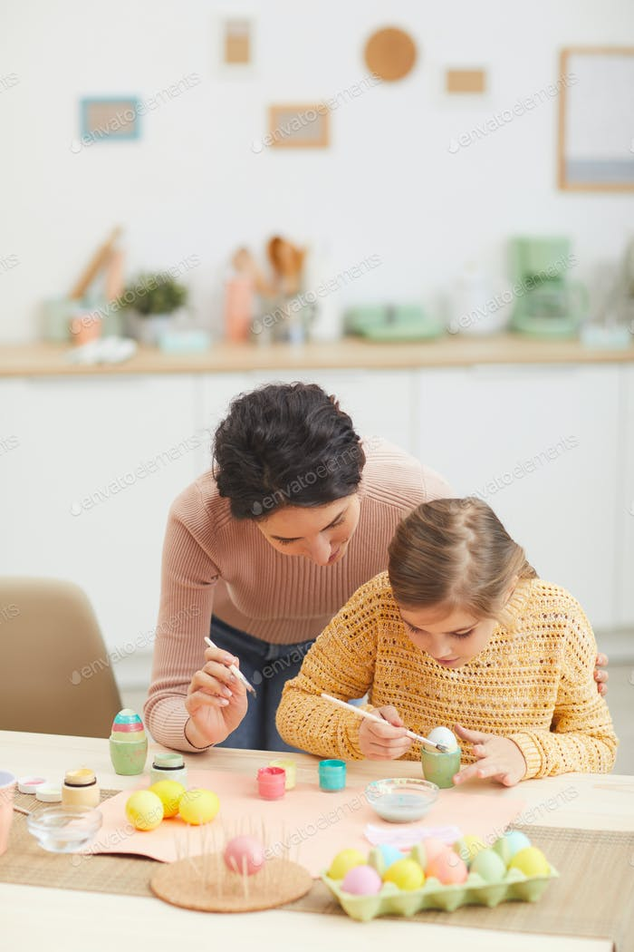 Caring Mother Painting easter Eggs with Daughter